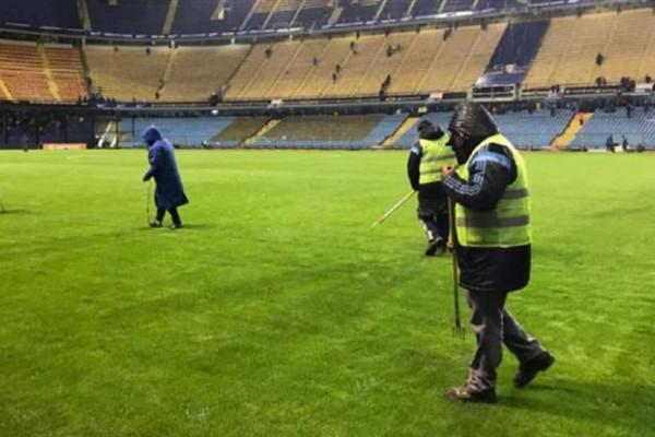 Empleados de Boca Juniors reacondicionan el césped donde jugarán Argentina y Perú por las Eliminatorias sudamericanas.